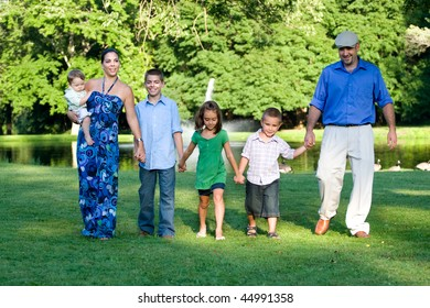 An attractive young family walking together through the park on a nice spring or summer day.