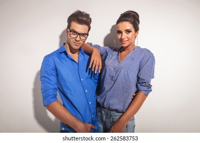 Attractive young fashion man embracing his girlfriend while looking at the camera.