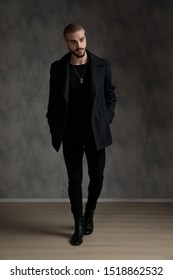 attractive young fashion man wearing black longcoat, looking to side, walking on grey background in studio, full body;