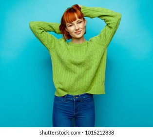 Attractive young fashion woman wear green sweater isolated on blue background