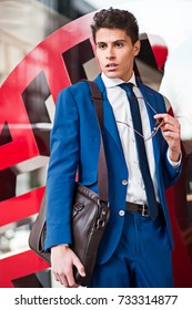 attractive young fashionable businessman standing in the street with a briefcase
