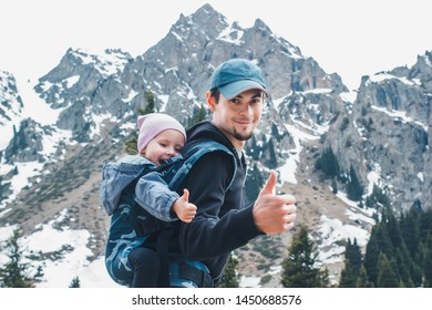 Attractive young father with her baby daughter in ergonomic baby carrier on back outside in mountain nature, show thumbs up.