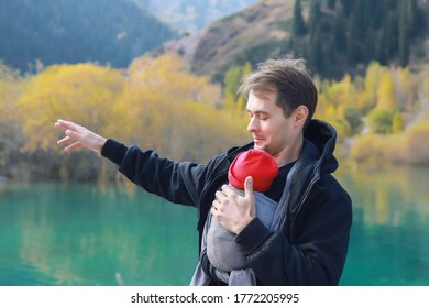 Attractive young father with her infant baby in sling outdoor. Man is carrying her child and travel in autumn mountain