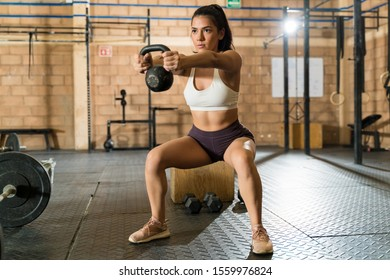 Attractive young female athlete doing squats while holding kettlebell at gym