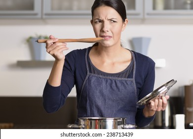 Attractive young female cook standing at the hob in her apron tasting her food in the saucepan with a grimace as she finds it distasteful and unpalatable