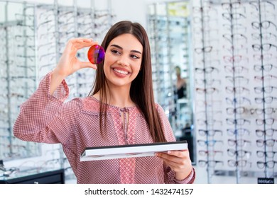 Attractive young female doctor in ophthalmology clinic showing different polarized lens.