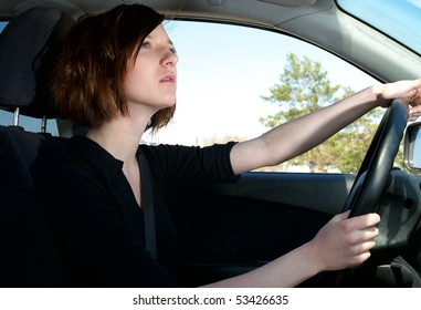 Attractive young female driving car look to the road
