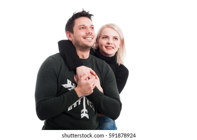 Attractive young female embracing his boyfriend from behind on white background with text space