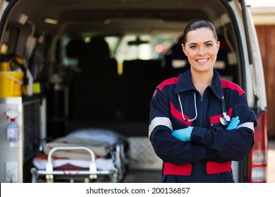 attractive young female emergency medical service worker in front of ambulance