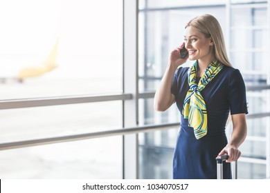 Attractive young female flight attendant is walking in airport terminal and talking on a smart phone.