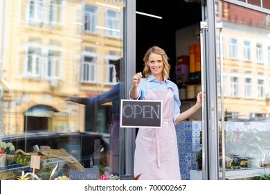 attractive young female florist in apron holding open sign and smiling at camera
