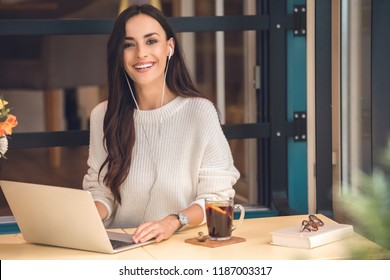attractive young female freelancer in earphones working on laptop and looking at camera at table with mulled wine in cafe
