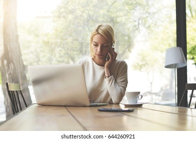 Attractive young female having smartphone conversation in modern loft interior with big windows and garden view, gorgeous businesswoman working at copy space wooden table with open laptop computer