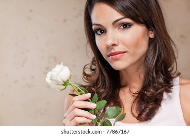 An attractive young female holding a white rose