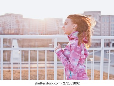Attractive young female with loose hair wearing pink windbreaker running on a sunset. Profile view. Inspirational photo. Retro coloring