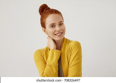 Attractive young female model with ginger hair, wearing yellow cape, keeping her hand on neck, looking with happy expression into camera, resting at home after hard-working day isolated on white wall