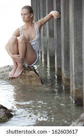 An attractive young female model wearing white shorts and a white top posing outdoors standing in the water.