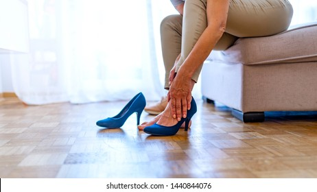 Attractive young female office worker finished work back to home sitting on sofa relaxing and feeling feet painful take off high heel shoes using hand massage. Woman with sore foot isolated on white