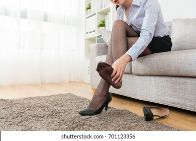 attractive young female office worker finished work back to home sitting on sofa relaxing and feeling feet painful take off high heel shoes using hand massage.
