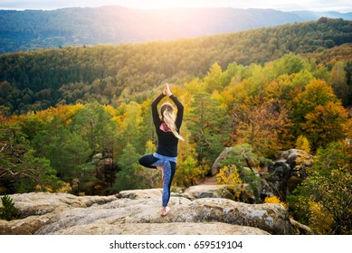 Attractive young female is practicing yoga and doing asana Vrikshasana on the top of the high rocky mountain in the evening. Autumn forests, rocks and hills on the background