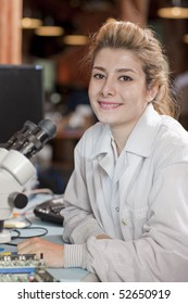 A attractive young female researcher in a lab coat is smiling as she sits in front of a microscope. Vertical shot.