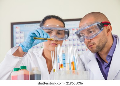 Attractive young female scientist and her male supervisor pipetting and microscoping in the life science research laboratory (biochemistry, genetics, forensics, microbiology..)
