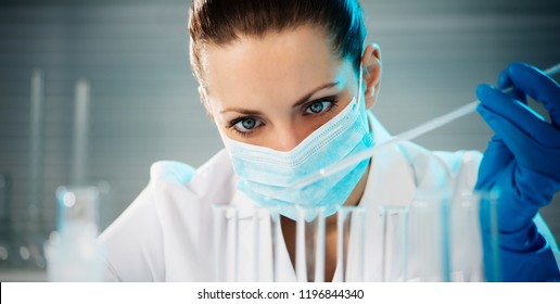 Attractive young female scientist working in laboratory. Horizontal image