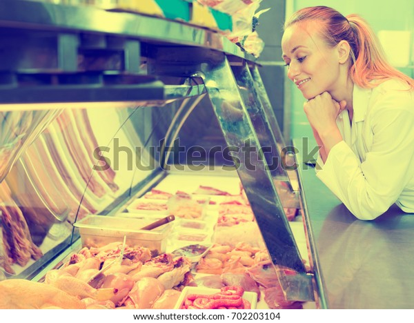 Attractive young female seller wearing uniform working with fresh meat in glass show case in shop