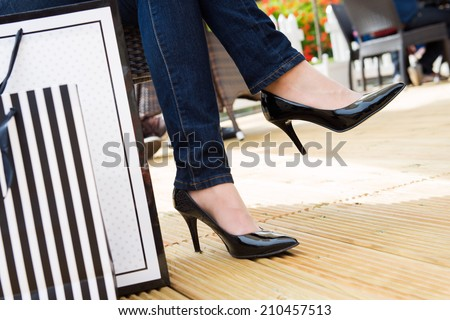Attractive young female in sexy black high heels enjoying a break after successful shopping, detail shot, with copy space