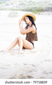 Attractive Young Female Sitting In White Sand At The Beach Looking Classy And Elegant In A Bikini And Sun Hat With Beautiful Expression
