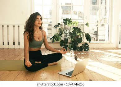 Attractive young female with slim body sitting barefoot with legs crossed, closing eyes, taking deep breaths while meditating after yoga practice in the morning, listening to calm music on laptop