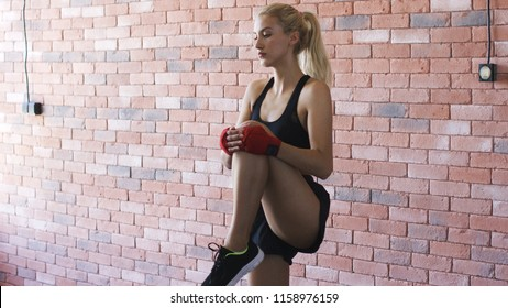 Attractive young female in sportswear doing warm-up exercise for legs while standing near brick wall in gym