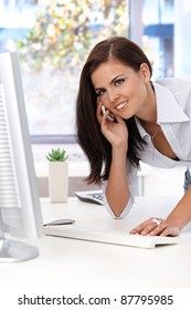 Attractive young female talking on mobile phone, working in bright office, smiling.?