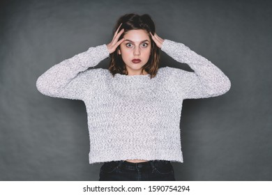 Attractive young female wearing sweater perplexedly looking at camera and touching hair with both hands while standing in studio on gray background