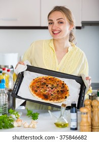 Attractive young female in yellow blouse cooking pizza at home