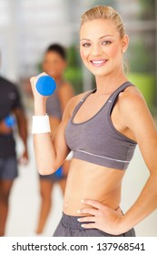 attractive young fit woman lifting dumbbell