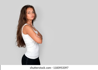 Attractive young fit woman on grey studio background. Casual woman crossed arm looking healthy and confident in white tank top. Free copyspace for text