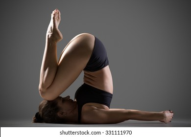 Attractive young fit woman in sportswear doing sport exercises, shoulderstand, variation of karna pidasana, Knee to Ear or Deaf Man Posture (variation of Raja Halasana), studio, gray background