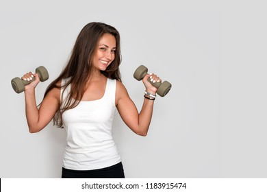 Attractive young fitness woman holding dumbells. Athletic girl doing a fitness workout with dumbbells on grey studio background
