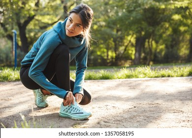 Attractive young fitness woman tying her shoelace outdoors