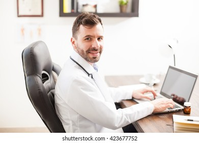 Attractive young and friendly Latin physician doing some work in a laptop computer in his office
