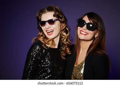 Attractive young friends wearing paillette dresses and sunglasses posing for photography against dark background, waist-up group portrait