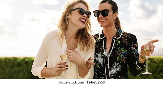 Attractive young friends with wine laughing outdoors. Two stylish women having a great time together.