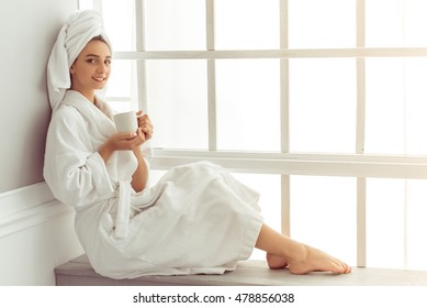 Attractive young girl in bathrobe and with a towel on her head is holding a cup, looking at camera and smiling while sitting on a window sill in the bathroom