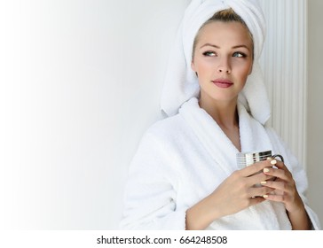Attractive young girl in bathrobe and with a towel on her head is holding a cup, looking to the side and smiling.Spa and Wellness. Girl in bathrobe drinking orange green tea in spa salon.