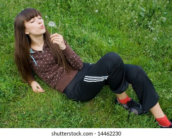an attractive young girl blows a dandelion