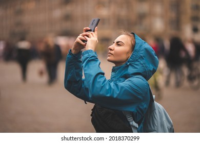 An attractive young girl in a blue jacket and blue backpack walks along the bridges of Amsterdam. Traveler girl enjoys the views of the city.