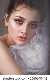Attractive young girl with bright colorful trendy smoky eyes, who hugs a big white air flower. Morning fresh look.