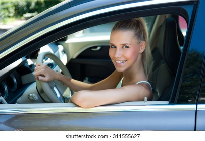Attractive young girl in car at drivers position