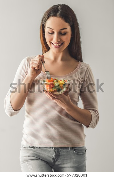 Attractive young girl in casual clothes is holding a salad and smiling, on gray background